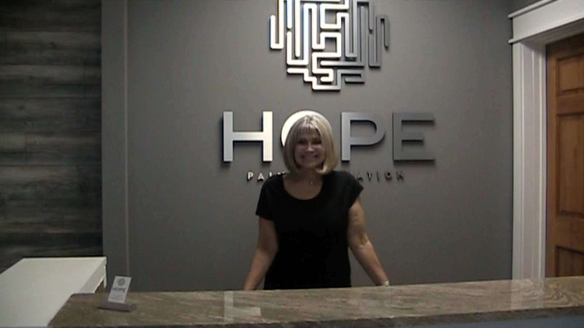 A woman standing behind the front desk of back pain center H.O.P.E. Pain Elimination in Miramar Beach, FL